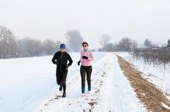 Hombre y mujer que corren en la nieve Foto de archivo libre de regalías