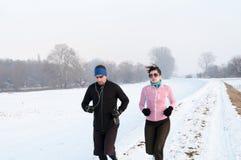 Hombre y mujer que corren en la nieve Fotos de archivo