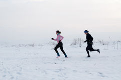 Hombre y mujer que corren en la nieve Imagen de archivo libre de regalías