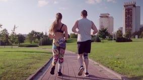 Hombre y mujer que corren en parque de la ciudad metrajes
