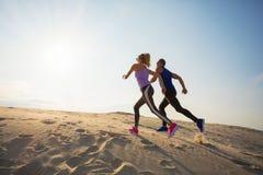 Hombre y mujer que corren hasta la colina imágenes de archivo libres de regalías