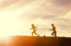 Hombre y mujer que corren junto en puesta del sol imagen de archivo libre de regalías