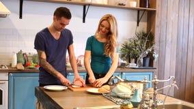 Hombre y mujer que cortan el pan y el jamón metrajes