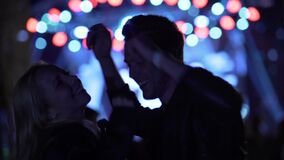 Hombre y mujer que cuelgan hacia fuera en el festival de música, disfrutando de vida de noche, relajación metrajes