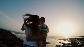 Hombre y mujer que defienden en la orilla el mar, abrazando y mirando en puesta del sol Pares en la playa de la tarde Cámaras len