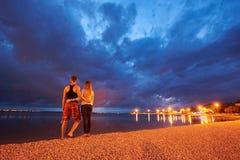 Hombre y mujer que descansan sobre Pebble Beach en la oscuridad en fondo azul dramático de cielo nublado del agua tranquila fotografía de archivo
