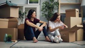 Hombre y mujer que desempaquetan después de mover en juntas tomar cosas desde la caja almacen de video