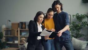 Hombre y mujer que discuten el contrato con el agente inmobiliario que habla y que lee el documento almacen de video
