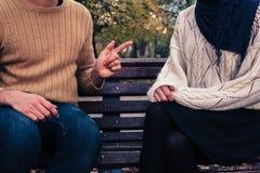 Hombre y mujer que discuten en parque Imagenes de archivo