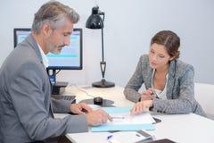 Hombre y mujer que discuten papeleo en oficina imagen de archivo libre de regalías