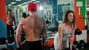 Hombre y mujer que doblan los brazos simult?neamente por las pesas de gimnasia de elevaci?n, entrenamiento en gimnasio almacen de video
