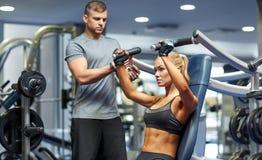 Hombre y mujer que doblan los músculos en la máquina del gimnasio imagenes de archivo