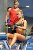 Hombre y mujer que doblan los músculos en la máquina del gimnasio Foto de archivo libre de regalías