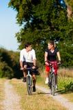 Hombre y mujer que ejercitan con la bicicleta Imagen de archivo