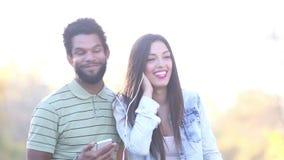 Hombre y mujer que escuchan la música junto, compartiendo los auriculares metrajes