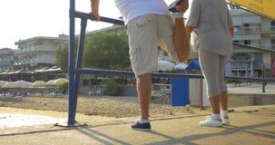 Hombre y mujer que estiran sus piernas al aire libre metrajes
