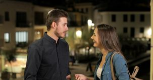 Hombre y mujer que hablan en la noche en la calle metrajes