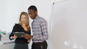Hombre y mujer que hablan, usando la tableta en oficina moderna almacen de video
