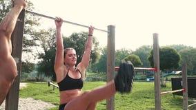 Hombre y mujer que hacen diversos ejercicios del peso del cuerpo en la barra horizontal metrajes