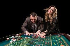 Hombre y mujer que juegan en la tabla de la ruleta en casino fotos de archivo