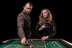Hombre y mujer que juegan en la tabla de la ruleta en casino imagenes de archivo