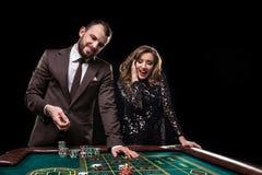 Hombre y mujer que juegan en la tabla de la ruleta en casino fotografía de archivo