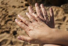 Hombre y mujer que llevan a cabo las manos con los anillos de bodas en fondo de la arena Imágenes de archivo libres de regalías