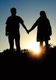 Hombre y mujer que llevan a cabo las manos en el fondo de un sol hermoso Foto de archivo libre de regalías