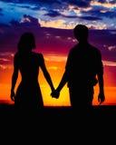 Hombre y mujer que llevan a cabo las manos en el fondo de un sol hermoso Fotografía de archivo libre de regalías