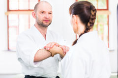 Hombre y mujer que luchan en la escuela de artes marciales del Aikido Imágenes de archivo libres de regalías