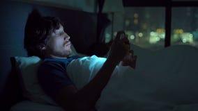 Hombre y mujer que mienten en cama, hombre con un smartphone mientras que está durmiendo la mujer el hombre apaga el teléfono y v almacen de video