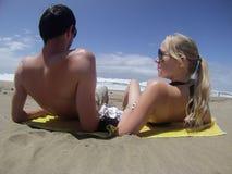 Hombre y mujer que mienten en la playa Imágenes de archivo libres de regalías