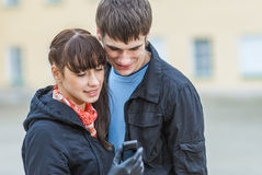 Hombre y mujer que miran el teléfono celular del SMS Imagen de archivo libre de regalías