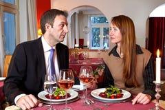 Hombre y mujer que miran fijamente cada uno sobre una comida Foto de archivo
