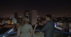 Hombre y mujer que miran la noche Tel Aviv del tejado del hotel, Israel almacen de metraje de vídeo