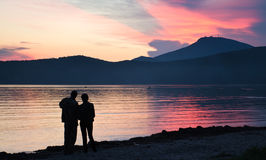 Hombre y mujer que miran la puesta del sol Fotografía de archivo libre de regalías