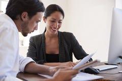 Hombre y mujer que miran los documentos en una oficina, cierre para arriba foto de archivo libre de regalías