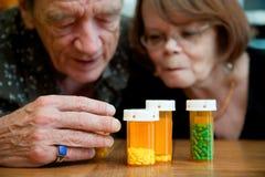 Hombre y mujer que miran medicaciones de la prescripción Foto de archivo libre de regalías