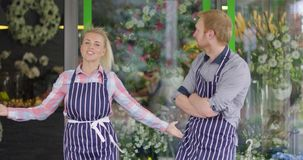 Hombre y mujer que presentan cerca de tienda floral almacen de video