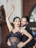 Hombre y mujer que realizan danza del tango en restaurante Fotografía de archivo libre de regalías