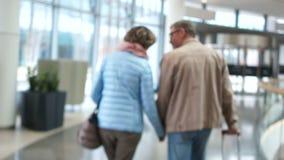 Hombre y mujer que salen con una maleta Incons?til colocado Un hombre abraza a una mujer por los hombros y la besa en almacen de video