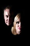 Hombre y mujer que salen de la obscuridad Imagen de archivo