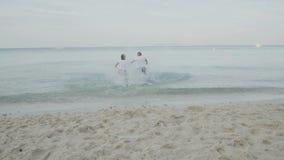 Hombre y mujer que saltan en el mar almacen de video