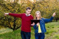 hombre y mujer que señalan en direcciones opuestas Imagen de archivo