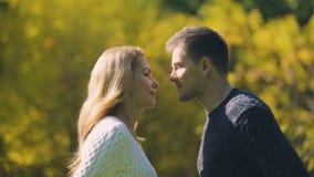 Hombre y mujer que se besan como ocultación detrás de la hoja del otoño, historia romántica, memorias metrajes