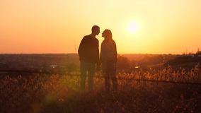 Hombre y mujer que se besan en la puesta del sol almacen de video