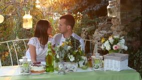 Hombre y mujer que se besan en la tabla del día de fiesta almacen de metraje de vídeo