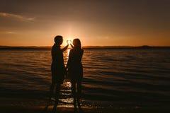 Hombre y mujer que se colocan en el mar en la puesta del sol foto de archivo