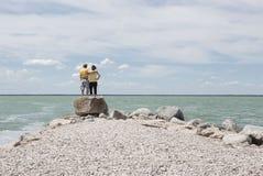 Hombre y mujer que se colocan en una roca grande al lado del lago y del abarcamiento Fotos de archivo libres de regalías