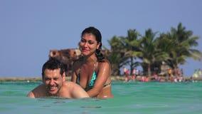 Hombre y mujer que se divierten que juega en agua del océano el vacaciones de verano metrajes